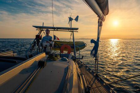 sailor steering sailboat at sunset, twilight time on the open sea Stok Fotoğraf