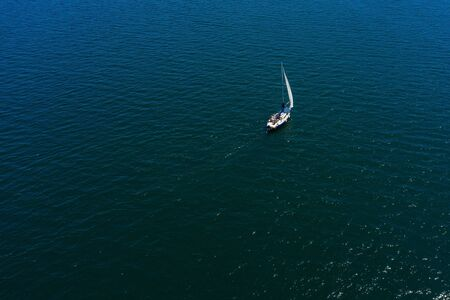 lonely white sailing yacht at sea, aerial view, drone shooting