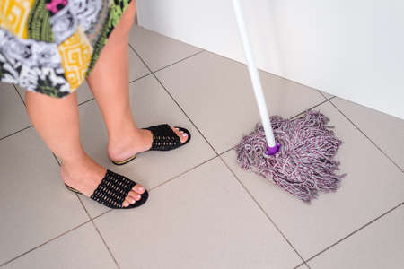woman washes tiles on the floor with a wet mop, housekeeping concept, close-up