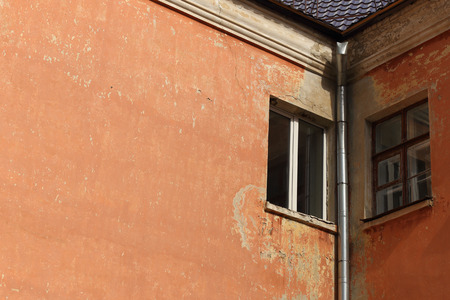 parget: Windows on the wall of an old house with paint and plaster peeling off