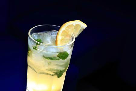 limonada: Vidrio de limonada con la rodaja de limón y menta. Fondo borroso Oscuro