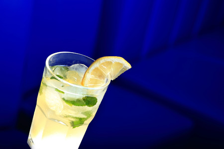 Glass of lemonade with the slice of lemon and mint. Blue blurred background photo
