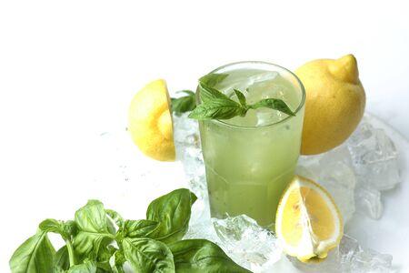 limonada: Vidrio de limonada con hojas de albahaca y limón en cubos de hielo aislados sobre fondo blanco.