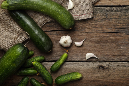 cocozelle: Zucchini, garlic and cucumbers on wooden background. Top view.