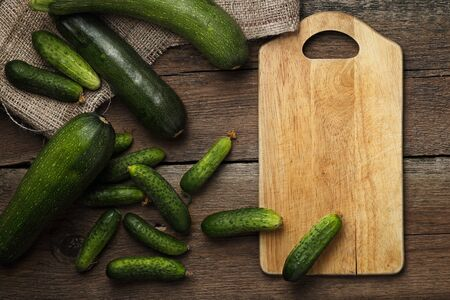 cocozelle: Zucchini and cucumbers on wooden background with kitchen board