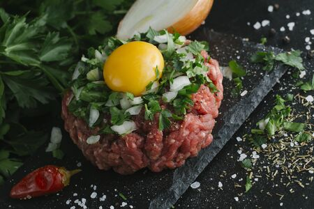Tartare steak. Beef raw chopped meat with spices, herbs and egg yolk. Fresh, spicy, delicious, gourmet meal on dark background with copy space, close-up.