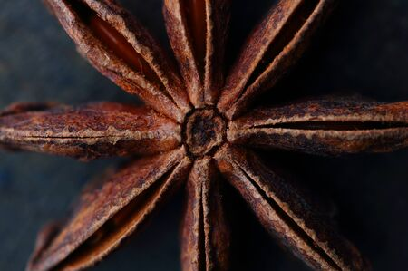 anis: Anise star seeds on the wooden background. Aromatic ingredient in culinary, raw for alcohol drink arak, ouzo, raki, sambuca. Macro, close-up.