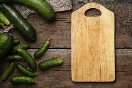 Zucchini and cucumbers on wooden background with kitchen board