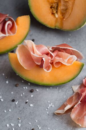Traditional Italian and Spanish salting, smoking, dry-cured dish - jamon Serrano and prosciutto crudo sliced with melon on grey background.