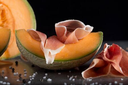 Jambon mix. Ham. Traditional Italian and Spanish salting, smoking, dry-cured dish - jamon Serrano and prosciutto crudo sliced with melon on grey background. Copy space. Closeup. Stock Photo