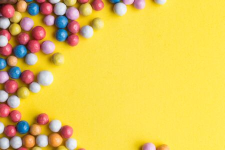 Candies colorful mix on yellow bright background with copy space top view