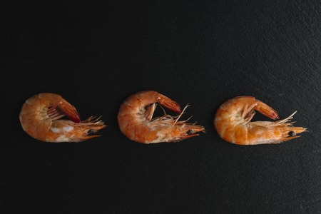 creole: Shrimps on black background. Delicious seafood appetizer served boiled or grilled with spices. Close up. Top view