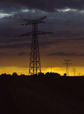 telephone poles: High voltage power lines and transmission towers at sunset. Poles and overhead power lines silhouettes in the dusk. Electricity generation and distribution. Electric power industry and nature concept