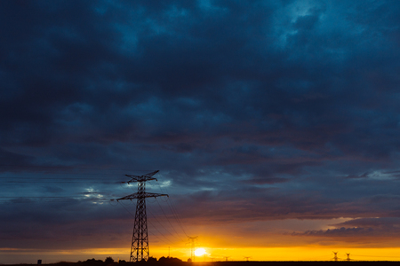 france station: High voltage power lines and transmission towers at sunset. Poles and overhead power lines silhouettes in the dusk. Electricity generation and distribution. Electric power industry and nature concept