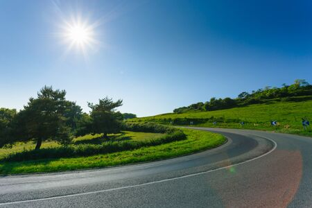 Empty asphalt curvy road passing through green fields and forests. Countryside landscape on a sunny spring day in France. Sunbeams in the sky. Transport, industrial agriculture, road network concept
