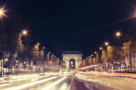Illuminated Arc de Triomphe and the avenue Champs-Elysees in Paris. Famous touristic places and transportation concept. Night urban landscape with street traffic and city lights. Long exposure. Toned