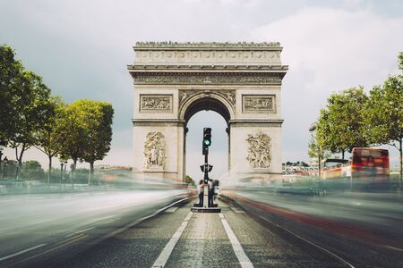 Famous avenue Champs-Elysees and the Triumphal Arch, symbol of the glory and historical heritage. Iconic touristic architectural landmark of Paris, France. Tourism and travel concept. Long exposure.