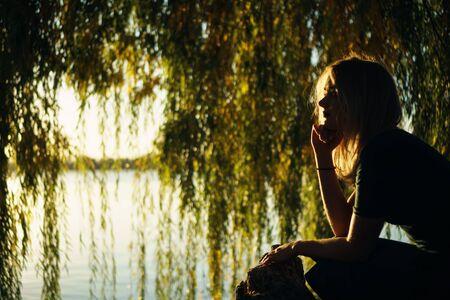 Jesienny portret uśmiechniętej młodej dziewczyny w pobliżu wierzby na tle jeziora o zachodzie słońca Zdjęcie Seryjne