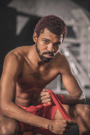 Dark-skinned young sportsman in a gym getting ready for the workout Imagens