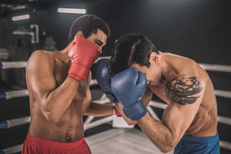 Two kickboxers fighting on a boxing ring and looking aggressive