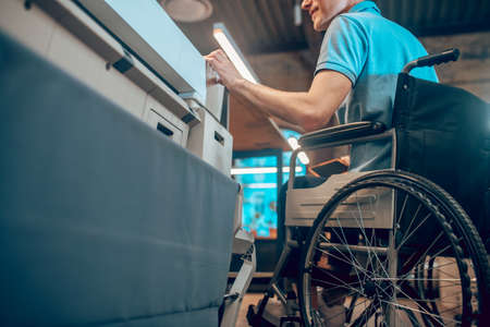 Man in wheelchair at copy center Foto de archivo