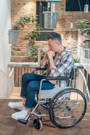 Sad young adult man on wheelchair indoors