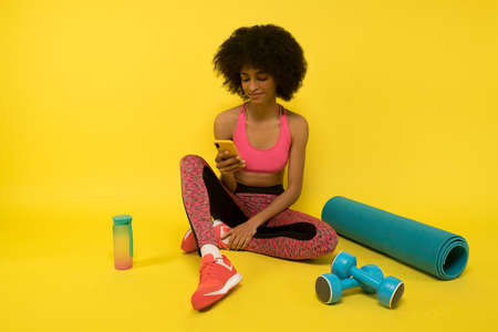A young pretty curly-haired mulatta resting after a workout