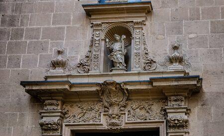 saint nicolas: Portal decoration of a boy with cross on Alicante cathedral Saint Nicolas, Spain Stock Photo