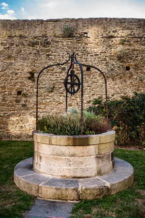 Decorative stone well with flowers and wheel in Saint-Malo, France