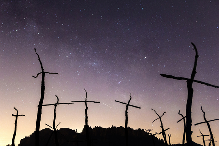 Silhouette of Montserrat mountains and crosses with the Milky Way on the background