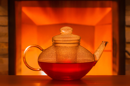 A glass teapot at the table in front of a fireplace Stock Photo