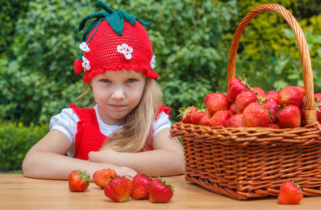 A funny little girl 4 years old with a basket of strawberries Stock Photo
