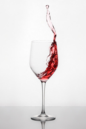 Splashing and moving red wine in the wineglass standing against light background with reflection on the stand Stock Photo