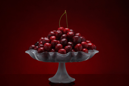 Pile of freshly washed sweet cherry fruits in a glass vase