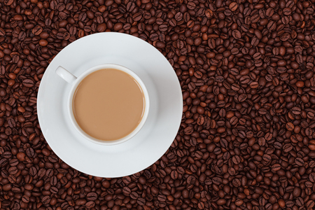 A cup of milk coffee on coffee beans background