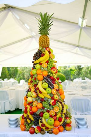 receptions: pyramid with tropical fruit on the wedding banquet  Stock Photo