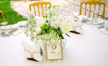 A view of a round banquet table with napkins and silverware set and a colorful flower centerpiece. photo