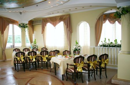 Elegant tables and chairs set up for a wedding banquet photo