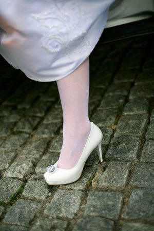 Wedding shoe bride emerging from the car after a trip  photo