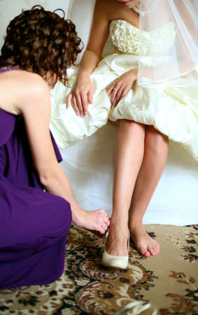 she helps a young bride, dresses her  photo