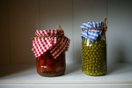 Canned green peas and tomatoes in the bank on the shelf in the pantry  photo
