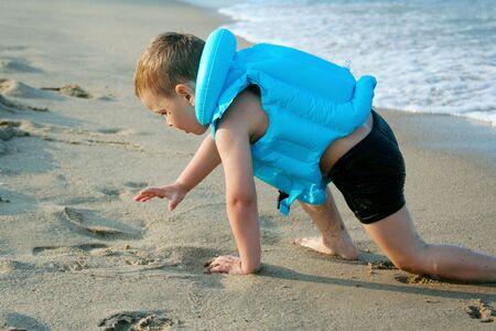 The boy crawls ashore from the sea, very utavshy, but very happy  photo