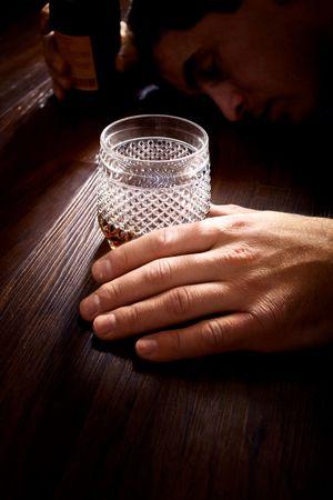 彼の手とガラスの瓶で床に横たわっている男 写真素材