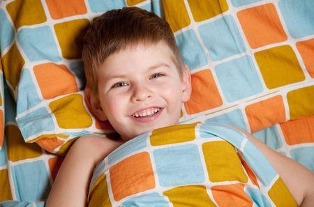 ベッドの中で陽気な男の子は睡眠を望んでいません。 写真素材