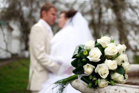 フォア グラウンド、バック グラウンドの新婚夫婦の結婚式のブーケ