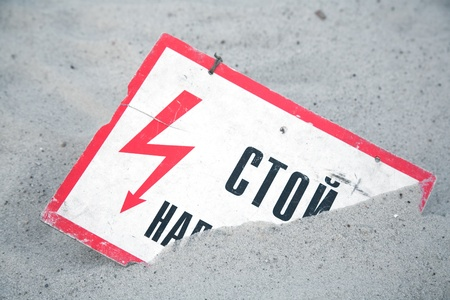 tension: Old sign of high tension lies in the sand