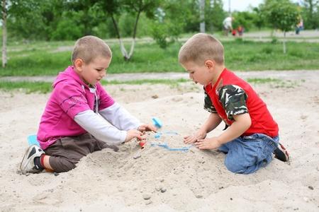 the sandbox: In the sandbox, boys buried the machine toy, fun game Stock Photo