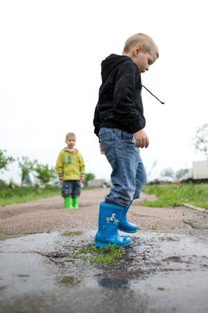 小さな男の子は水たまりに船で遊ぶ