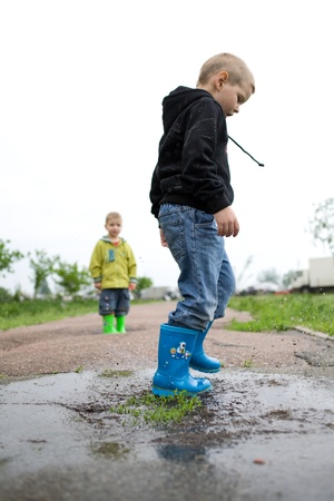 little boy plays with ship in the puddle photo