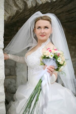 Young bride standing beside the stone wall of an ancient castle photo